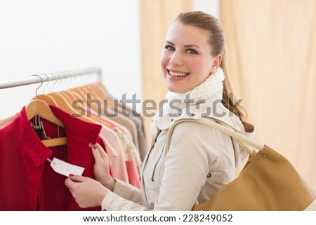 Pretty shopping blonde smiling at the camera in the store - stock photo