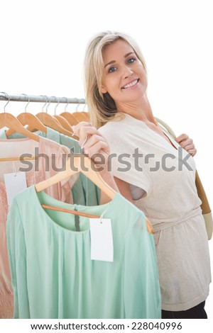 Pretty shopping blonde smiling at the camera on white background