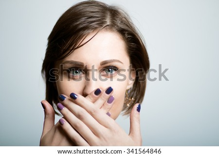 Pretty slender girl covers her mouth with her hands, lifestyle, isolated on a gray background - stock photo