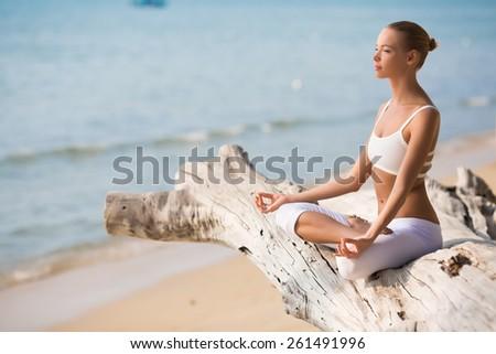 Pretty slim Woman in white costume doing Yoga pose near big tree - stock photo