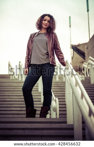 Pretty, slim young woman posing on stairs; fashion and beauty