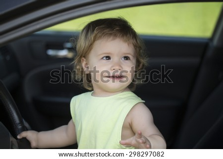 Pretty small funny male child driver sitting in big car with black salon holding wheel looking away through window in summer, horizontal picture - stock photo