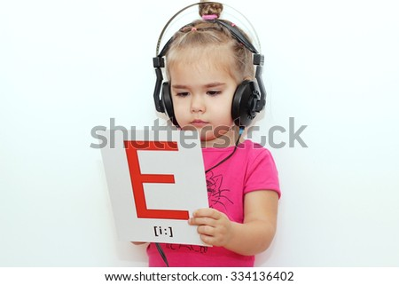 Pretty small girl in the earphones reading a sheet of paper with E letter like printed music over white background, indoor portrait
