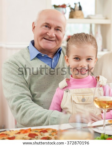 Pretty small girl is visiting her grandfather - stock photo