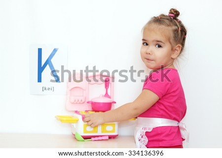 Pretty small girl playing with a toy kitchen over white background with D letter on it, indoor portrait - stock photo
