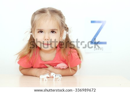 Pretty small girl playing with two tiny toy zebras over white background with Z letter on it, indoor portrait, ABC concept - stock photo