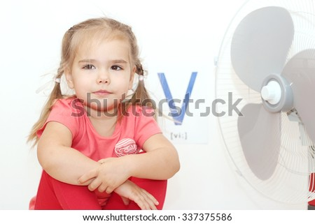 Pretty small girl sitting near the electric fan (ventilator) over white background with V letter on it, indoor portrait, ABC concept - stock photo
