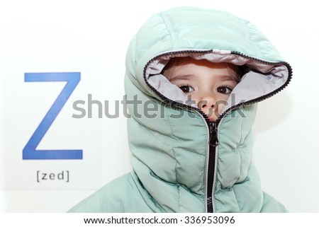 Pretty small girl wearing a hood of the winter coat with zipper over white background with Z letter on it, indoor portrait, ABC concept - stock photo