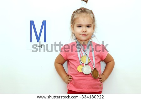 Pretty small girl with several medals on her neck over white background with M letter on it, indoor portrait - stock photo