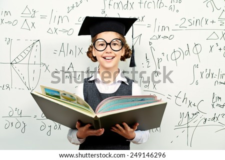 Pretty smart schoolgirl in big glasses and academic hat stands with opened book at the blackboard. Education. - stock photo