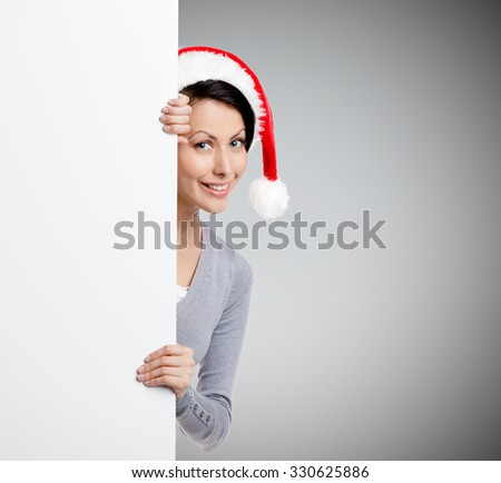 Pretty smiley woman peeps out through the wall, wearing Christmas red cap, isolated on grey - stock photo