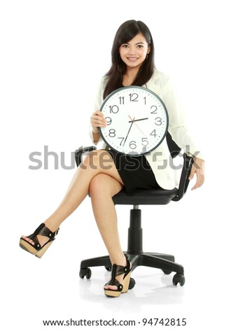 Pretty smiling asian business woman waiting holding a clock - stock photo