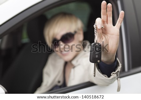pretty smiling blond girl with short hair sitting in her new car and shows the keys - stock photo