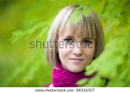 Pretty smiling blonde girl on the background of foliage of a trees.