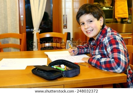 Pretty smiling boy does homework at his home