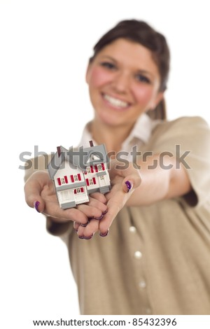 Pretty Smiling Ethnic Female Holding Out Small House in Front Isolated on a White Background - Focus is on the House. - stock photo