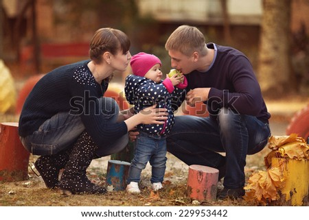 Pretty smiling family and daughter in autumn park - stock photo