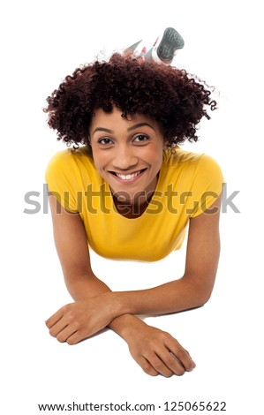 Pretty smiling female model with curly hair relaxing on the floor. - stock photo