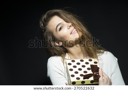 Pretty smiling girl holding spotted present box standing on black background copyspace, horizontal photo - stock photo