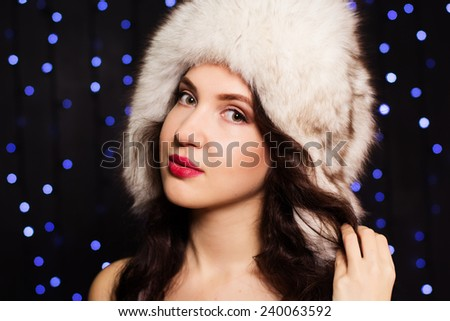 Pretty smiling girl in a furry winter hat