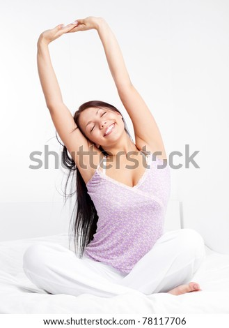 pretty smiling girl sitting on the bed at home waking up and stretching