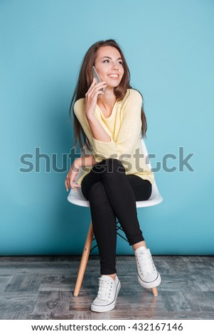 Pretty smiling girl talking on the smartphone and sitting on the chair isolated on a blue background - stock photo