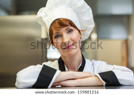 Pretty smiling head chef looking at camera in professional kitchen - stock photo
