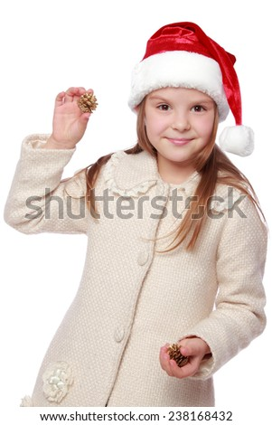 Pretty smiling little girl in Santa's red hat holding a Christmas pine cone/Image of happy young girl in a Santa hat enjoys and laughing on white background - stock photo