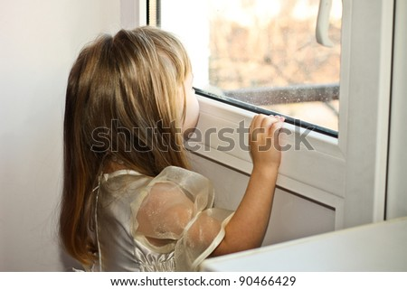 pretty smiling little girl on balcony, look from window - stock photo