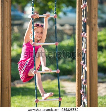 Pretty smiling  little girl on outdoor playground equipment - stock photo