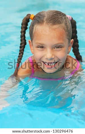Pretty smiling little girl swims in children's pool.