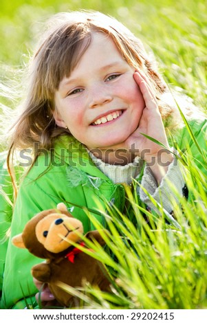 Pretty smiling little girl with toy on green grass - stock photo