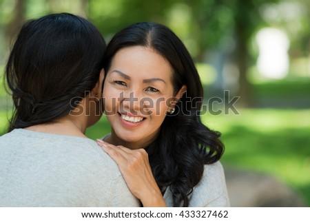 Pretty smiling mature woman hugging her female friend - stock photo