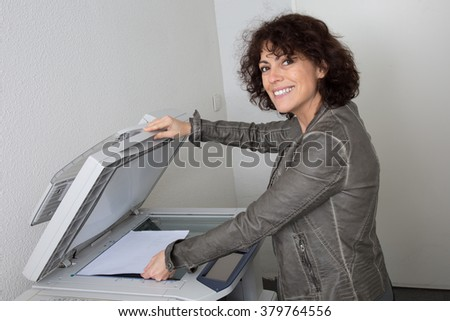 Pretty smiling secretary using a copy machine at work - stock photo