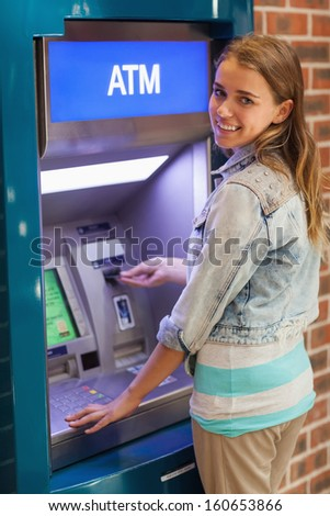 Pretty smiling student withdrawing cash at an ATM - stock photo