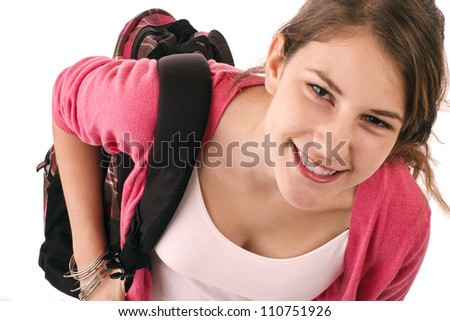 Pretty smiling teenage girl in fashionable back to school clothes carries backpack over shoulder. Pink sweater, tank top, black short skirt. Vertical, isolated on white, copy space.