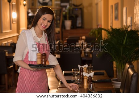 Pretty smiling waitress serving table in the restaurant