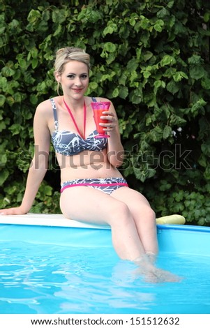 Pretty smiling woman at the pool sitting on the edge in her bikini sipping a tropical cocktail - stock photo