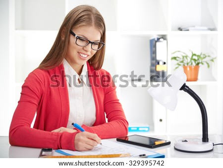 Pretty smiling woman designer drawing on paper and using digital tablet in the office. Female architect estimating construction plan. - stock photo