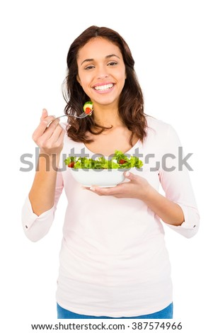 Pretty smiling woman eating salad on white background