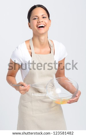 Pretty smiling woman home chef beating eggs with whisk and glass bowl for baking or food preparation - stock photo