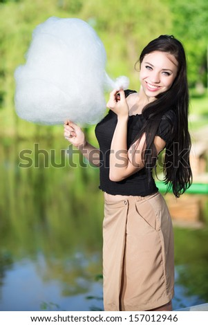 Pretty smiling woman posing with a cotton candy near the pond - stock photo