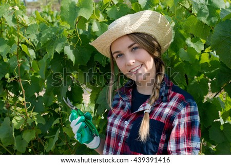 Pretty smiling woman pruning plant - stock photo