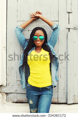 Pretty smiling young african woman in colorful clothes and sunglasses - stock photo