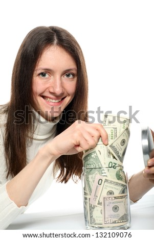 Pretty smiling young woman taking dollars from a glass jar; isolated on white