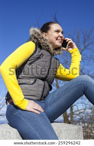 Pretty smilling young woman using smart cellphone outdoors on sunny  windy day, against dark blue sky, space for text - stock photo