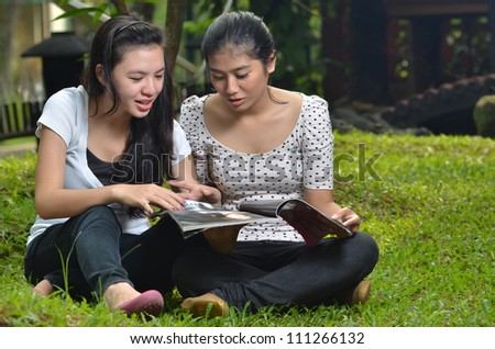 Pretty southeast asian girls  reading and sharing  information  on a book or magazine with happy expression at outdoor scene