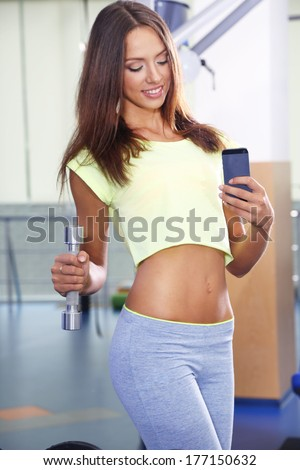 Pretty sporty girl photographing herself in mirror at phone in gum - stock photo