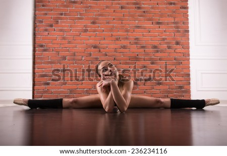 Pretty sporty strong slim and fit young woman sitting, doing split and stretching exercises, sitting on a full split. In studio, against brick wall, mirror reflection on the floor - stock photo