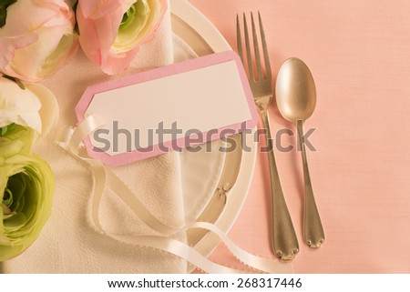Pretty Spring Placesetting with Pastel Flowers, white plates, fork, spoon and namecard with ribbon on pink tablecloth background with room or space for copy, text, your words.  Horizontal above view - stock photo